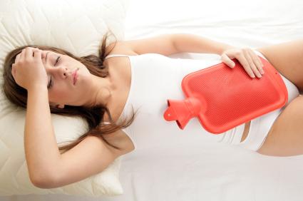 Femme allongée avec une bouillotte sur le foie